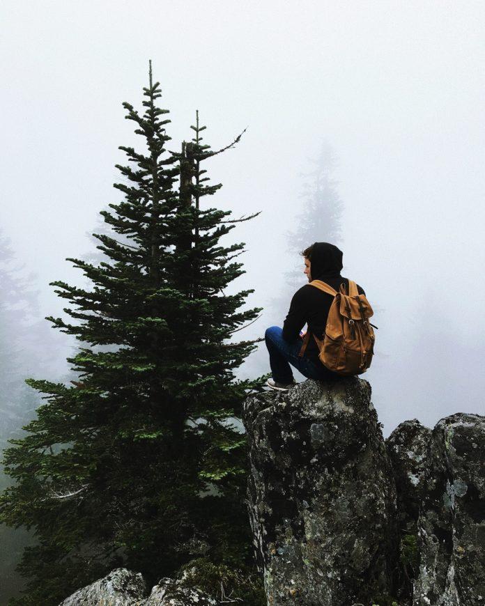 Tânăr singur pe munte, uitându-se în zare