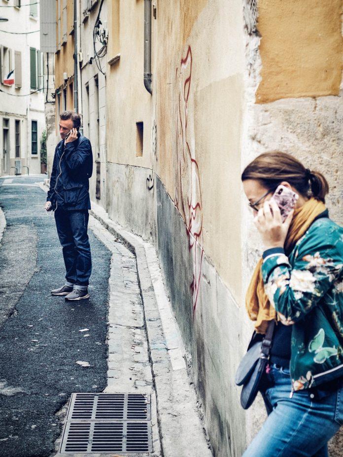 Bărbat și femeie vorbind separat la telefon