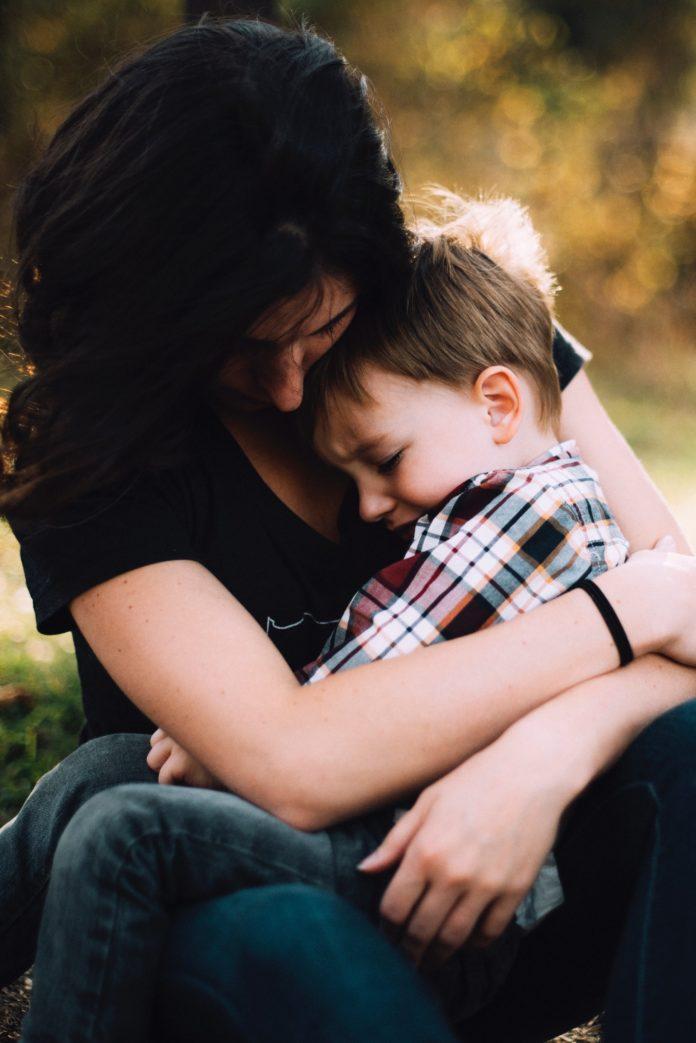 Mamă ținându-și copilul în brațe