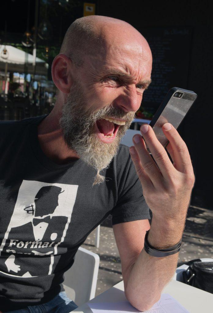Bărbat țipând la interlocutorul din telefon